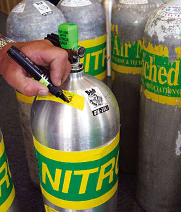 scuba diver marking their enriched air scuba cylinder with a black marker
