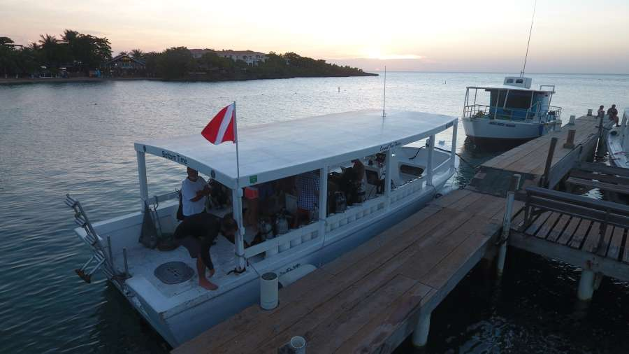 a large covered scuba diving boat with a dock to walk on and a large ladder to climb aboard