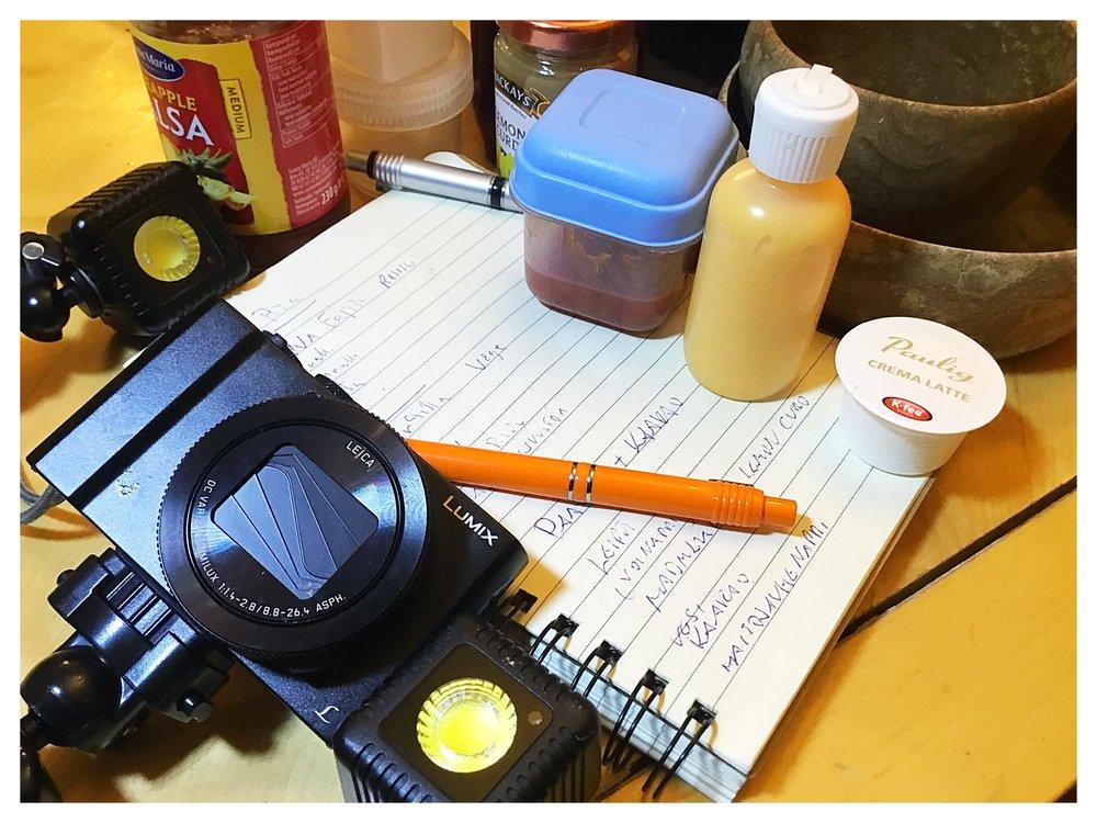 Päivän hommiin tarvittiin mm. Lumecube-valoja ja Lumix-kameraa. Vihkossa on päivässä tarvittavat muistiinpanot ja ympärillä juttuun tulevia tuotteita.