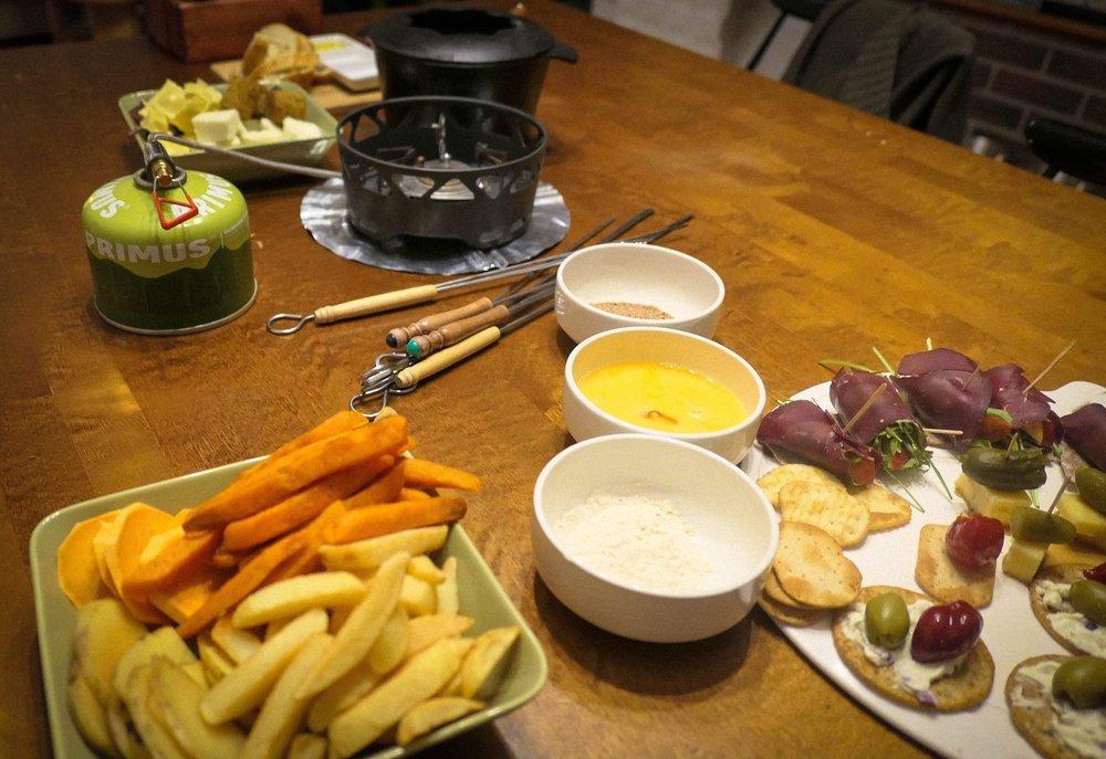 Kotini ruokapöydällä fondue-pataa lämmitetään retkikeittimellä ja testissä on mahdollisia juttuun tulevia herkkuja.