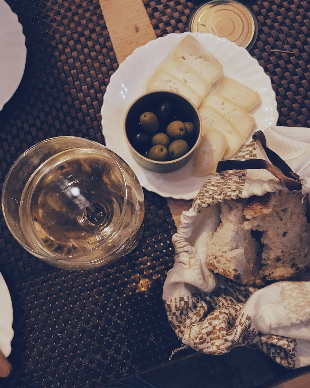 Delicious crusty bread, tasty soft cheese, olives, and a strong white wine