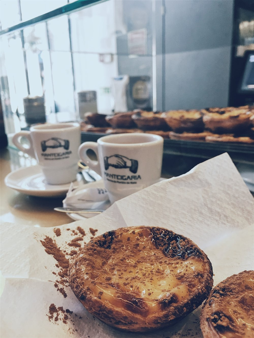 Two pasteis de nata and two espressos