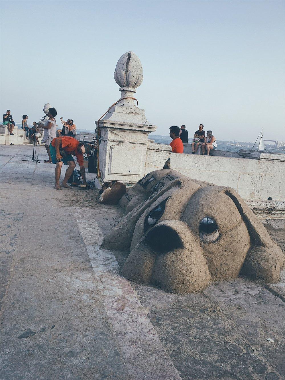 Street musicians and a sand artist