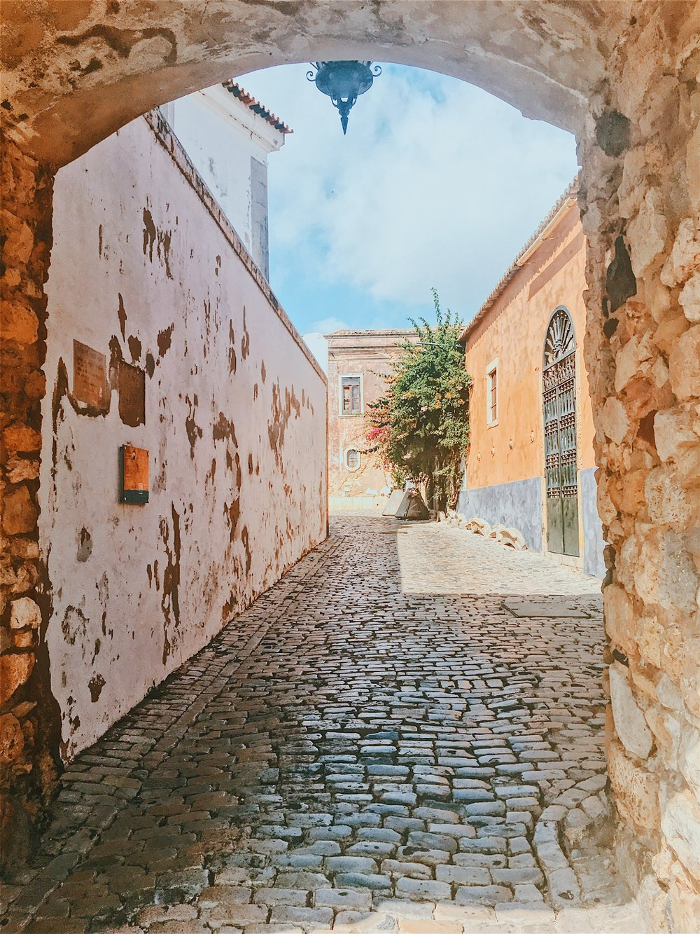 A beautiful archway over a cobblestone street