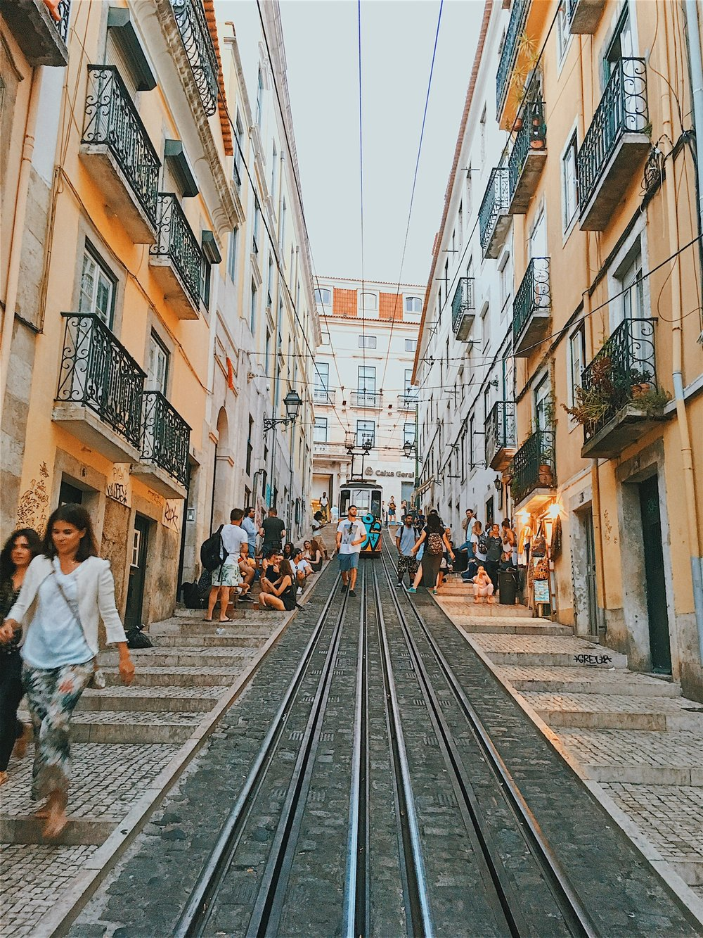 """Looking up the """"party hill"""" from about a quarter of the way down; our apartment was at the top of the last building on the right. You can see people beginning to congregate for the nighttime revelry (it doesn't get dark in Lisbon during the summer until past 9pm)"""