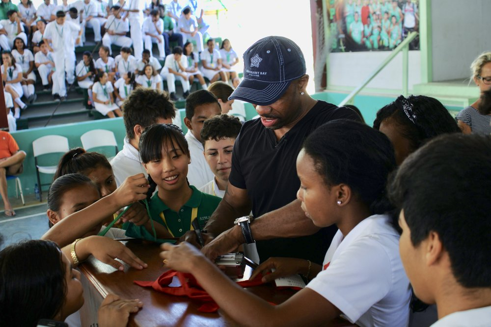 Ray Crockett signs autographs for young fans after his speech at San Pedro High School on Ambergris Caye, Belize.