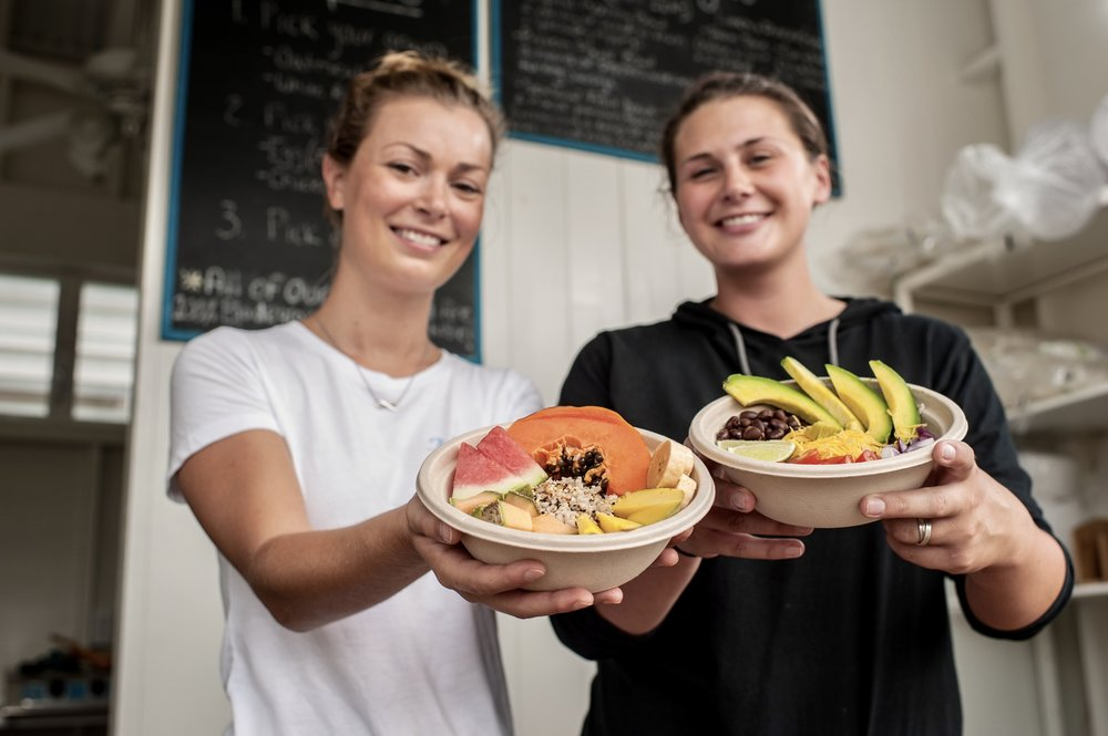 Niki Lamparelli and Colleen Clifford proudly display two of The Hive's menu items, a breakfast bowl and a Mexican quinoa bowl.