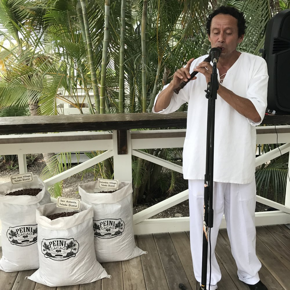 Local flute player, Pablo Collado, adds ambiance with his ethereal music. Beside him are cacao beans from three different farms in Toledo, Belize that Mahogany Chocolate sources from.