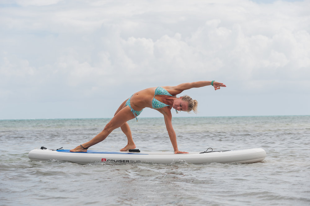 Yoga instructor Kerry Ann from Science and Soul Wellness practices paddleboard yoga at the Mahogany Bay Beach Club.