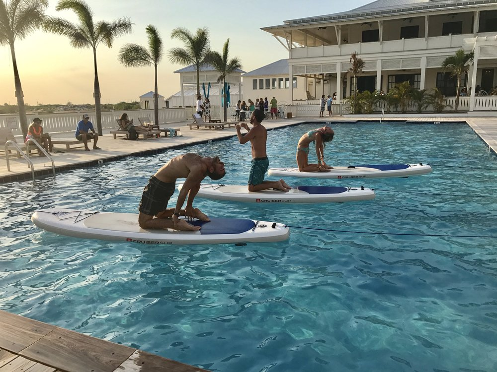 Spectators participate in paddle board yoga at the Science & Soul Wellness grand opening party at Mahogany Bay Village on May 6, 2017.