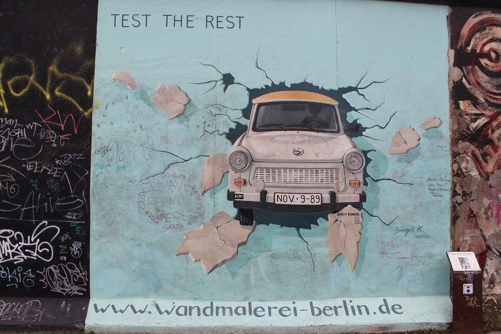 This depicts the most commonly used car in East Berlin, the Trabant, breaking through the Berlin Wall. The quote was originally 'Test The Best' but changed to 'Test The Rest' when the wall was restored in 2009.