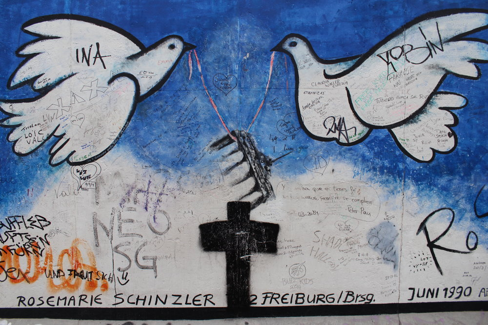 "Rosemarie Schinzler, originally from the German city of Freiberg, painted this mural ""Wachsen Lassen"", showing two doves lifting Brandenburg Gate and a cross."