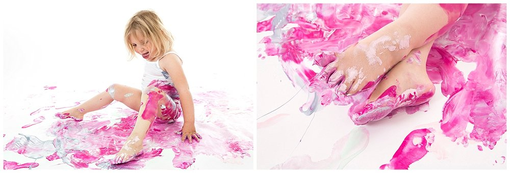 Andrea-Burolla-Photography-Denver-childrens-photographer-paint-session-messy-toes-handprints-foortprints-pink-tongue-out.jpg