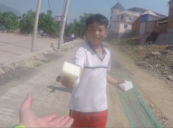 Village kid handing out water-soaked sponges, Tianjin, China