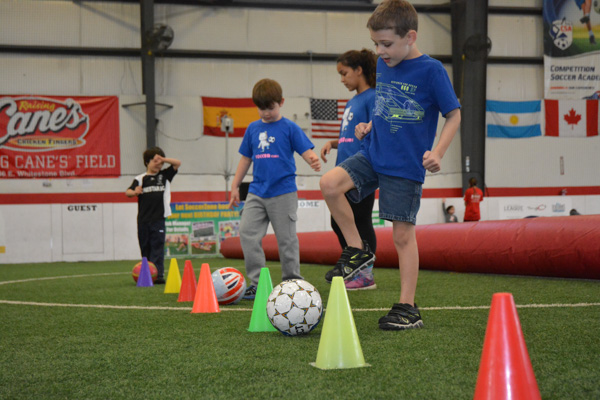 Kids practice weaving soccer balls through cones