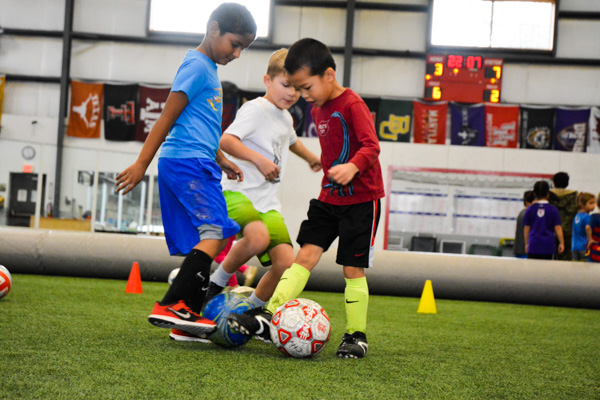 Three boys dribbling soccer balls