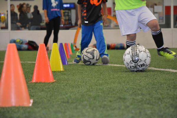 Children Dribble Soccer Balls Between Cones