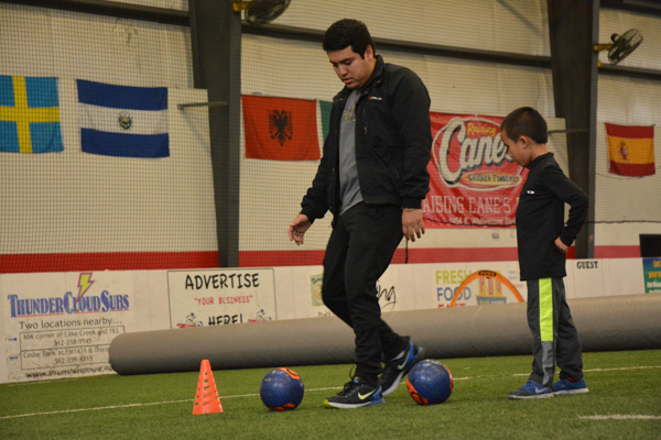 Coach Demonstrates Soccer Drill to Student