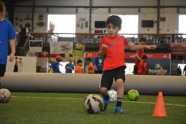 Boy in Red Shirt Dribbles Soccer Ball