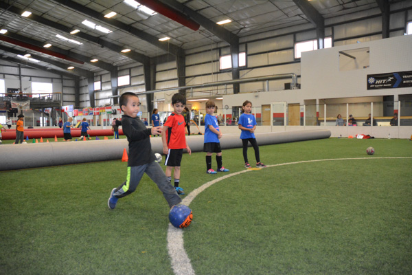 Boy Runs with Soccer Ball While Students Watch
