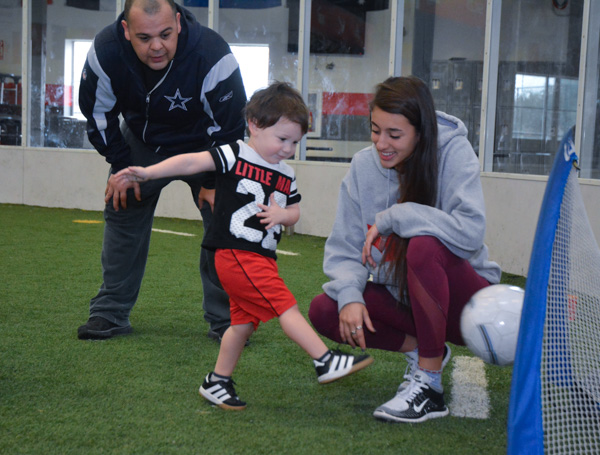 Parent and Coach Help Boy Shoot Ball Into Goal