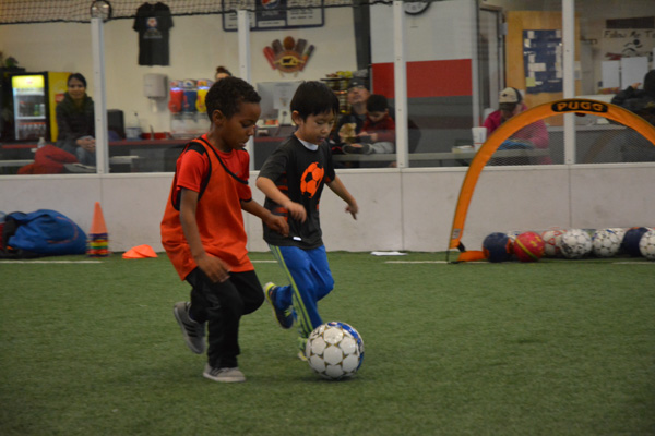 Two Boys Run With Soccer Ball