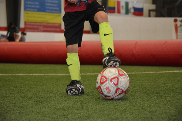 Boy Wearing Cleats With Foot On Soccer Ball