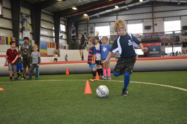 Boy Winds Up to Kick Ball