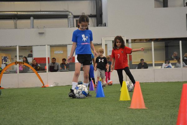 Girl Weaves Soccer Ball Through Cones