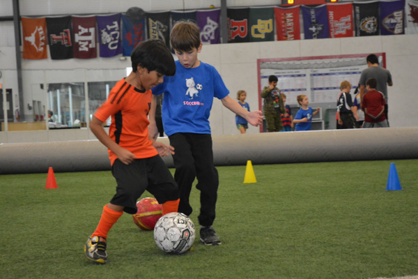 Two Boys Compete for Soccer Ball