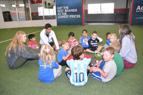 Soccer Cubs Sit in a Circle with the Coaches