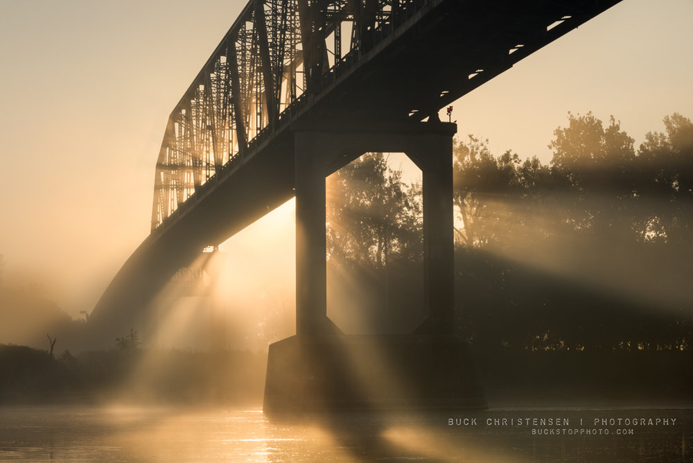 Fog at sunrise under toll bridge, Haworth Park, Bellevue, Nebraska.