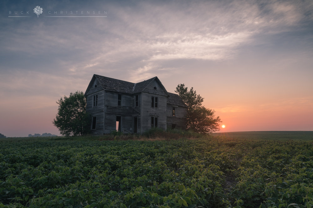 Abandoned farmhouse at sunrise in rural Iowa.