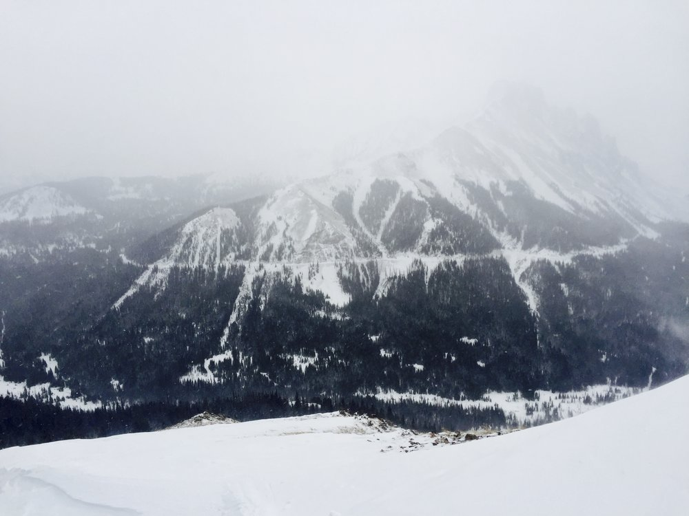 Looking from South Diamond Peak towards Nokhu Crags, with Michigan Ditch traversing the entire slope through the low-hanging clouds.