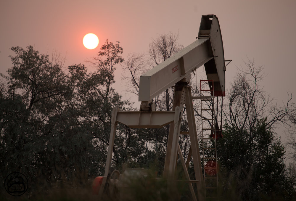 USA. Fort Collins, Colorado. September 4, 2017. An oil well operates near a residential neighborhood as the sun is shrouded in smoke from a recent forest fire.