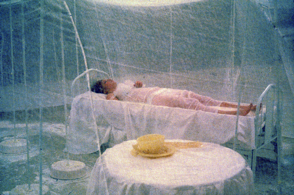 Under the Skirt   Installation/performance, Epperson Auditorium, Kansas City Art Institute  1992   15' dress held up with steel armature and poles with cake bases, table with beeswax teacup and saucer leaking hot honey, narrow bed filled with milk, and powdered sugar