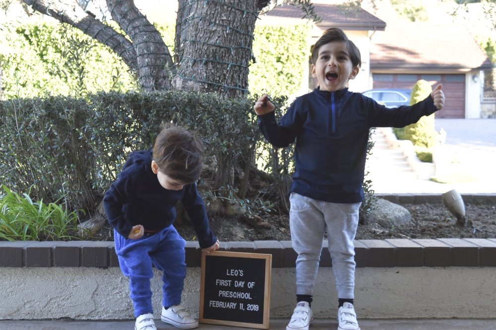 Brothers posing with letter board in front of tree on first day of preschool.