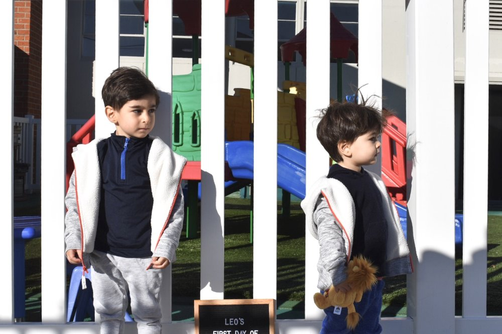 Brothers posing with letter board in front of preschool playground.
