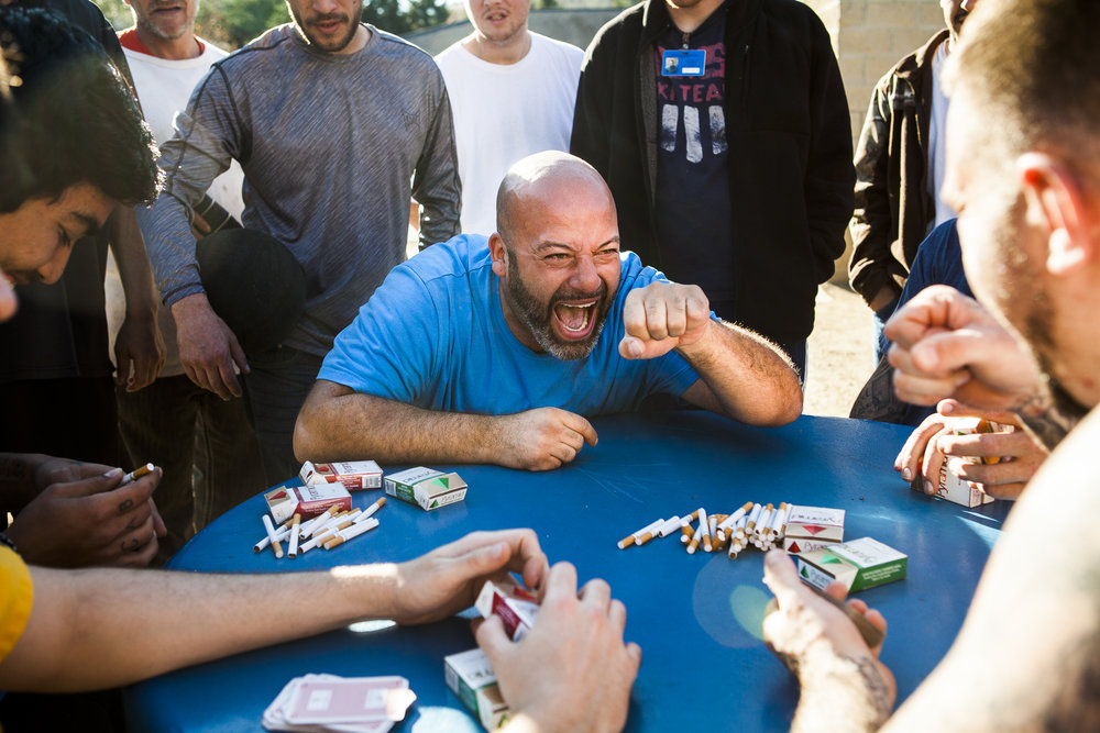 "Aaron Kline celebrates a win with Jason Cook as they play a form of poker for a pool of cigarettes at SEPTA Correctional Facility on November 18, 2016.  Chris Streeter, far left, ended up winning the pool of cigarettes, a total of 11 packs, and plans to use them to trade for a ""pick and poke"" (tattoo)."