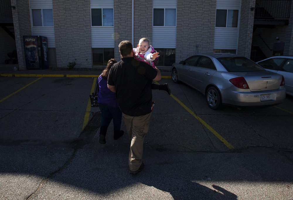 Cassie waves goodbye to Pastor Henderson after he drops them off at their apartment complex in Parkersburg, West Virginia. The church drives the family back and forth from their home so they can attend the Sunday Service.