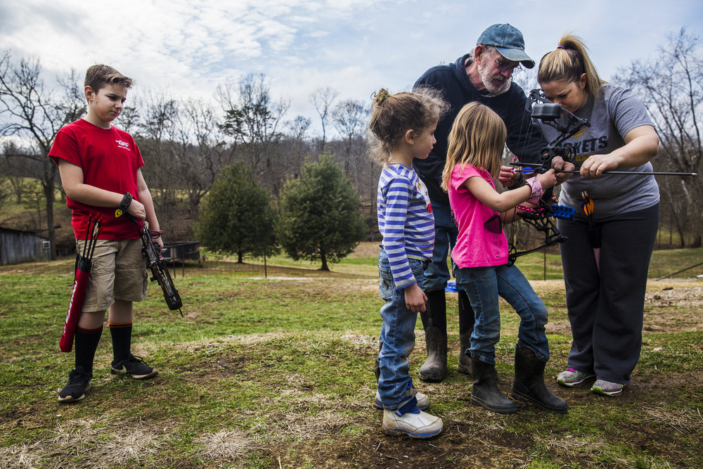 Luke Jonas waits to shoot his bow while his mother and grandfather coach his sister Emily on how to hold her bow.