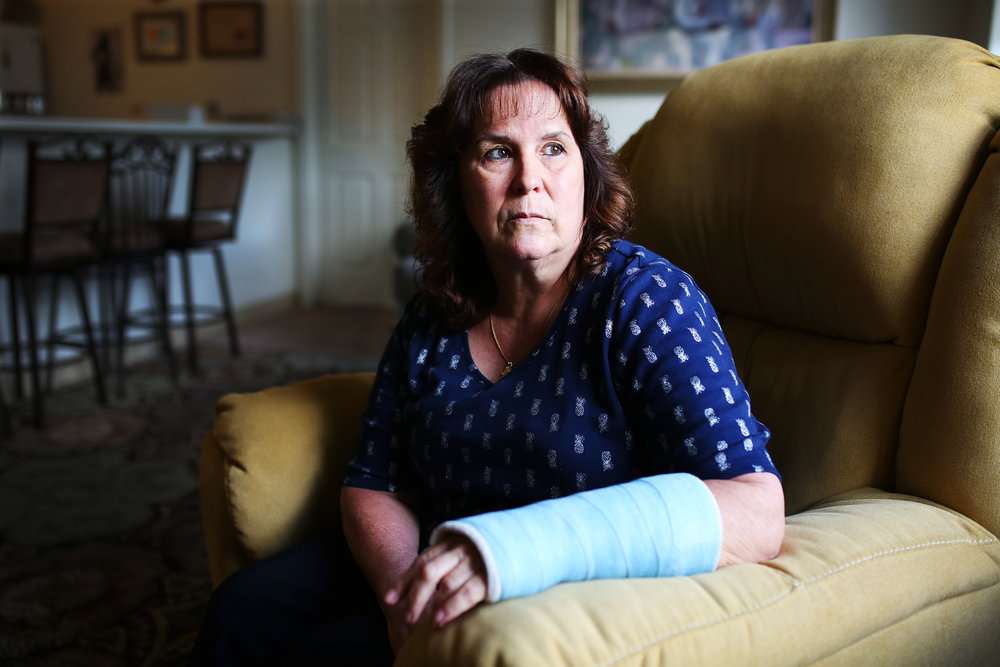 Bernadette Coughlin sits in her living for a portrait nearly one month after she fell and broke her wrist while at work. After the fall, Bernadette was required to take a drug test and her occasional recreational marijuana use led to a positive result. She then lost her job.