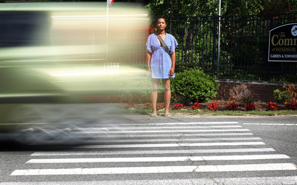 Lorre Mitchell stands for a portrait by the crosswalk where she was hit a as she crossed the street to take the bus to school.