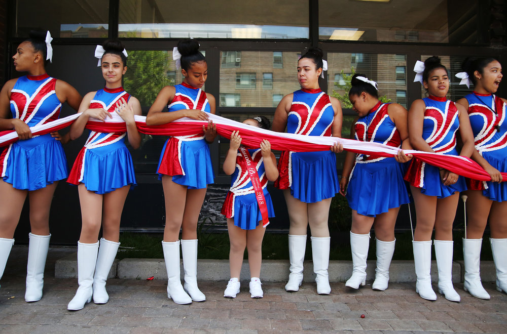 Members of Estrella Tropical prepare to open the Puerto Rican flag at the Festival Tetances Parade, part of the Festival Betances. Named after Ramón Emeterio Betances, a Puerto Rican patriot whose medical contributions benefited Latin America, Festival Betances celebrates its 50th anniversary this year.