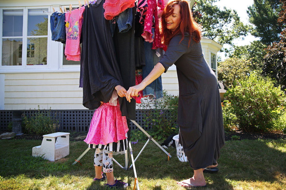 Jennifer Wilson hangs up laundry with her 7-year-old daughter, Sawyer, in their backyard. Due to the effects of the National Grid lockout, Jennifer and Sawyer have been without gas for four weeks.