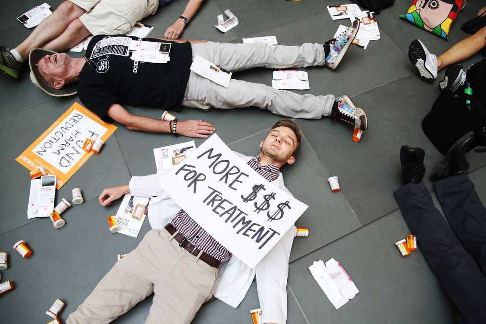"Micah Johnson, center, a fourth year medical student at Harvard University, participates with other Demonstrators in a ""die-in"" in the center of the Harvard Art Museum's atrium during a rally lead by Photographer Nan Goldin. The demonstration was held at the Harvard Art Museums to protest the benefactor of the Sackler Art Museum, who was a founder of a pharmaceutical company that has made vast profits selling opioids."