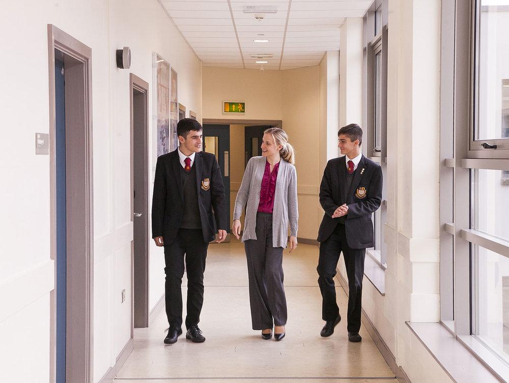 Students-with-female-teacher-corridor-happy-1600-2.jpg