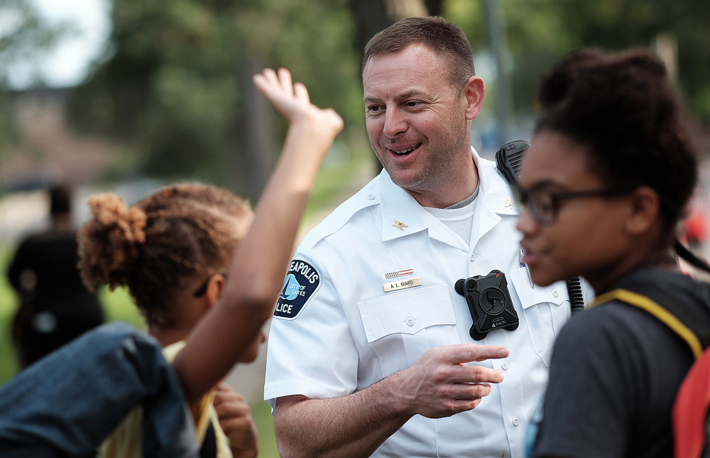 New Fourth Precinct Inspector Aaron Biard talks with Ascension Catholic School students at their back to school block party on August 24. Photo by David Pierini