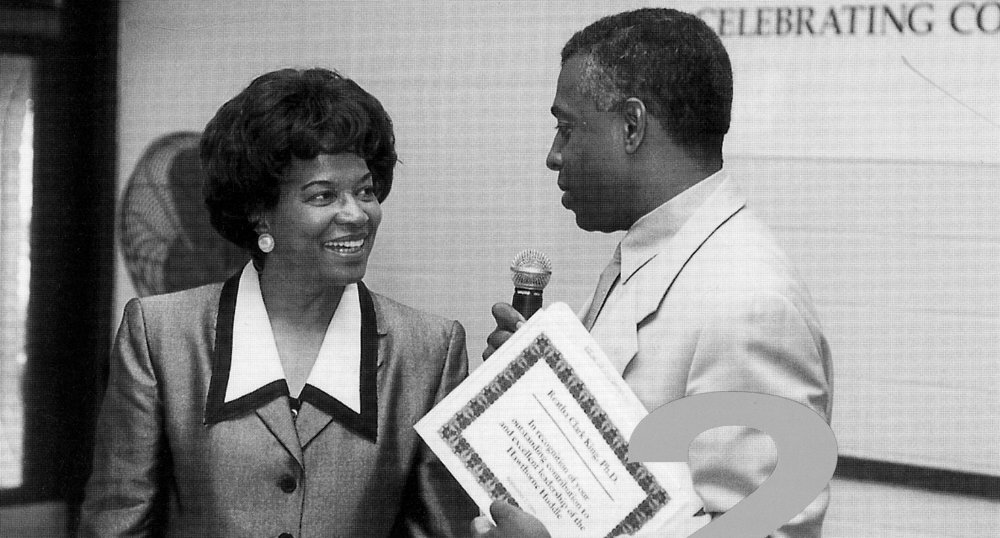 US Attorney for Minnesota Todd Jones presents former longtime Hawthorne Huddle leader Reatha Clark King with an award of appreciation in 1999.  Photo courtesy of the General Mills Archives.