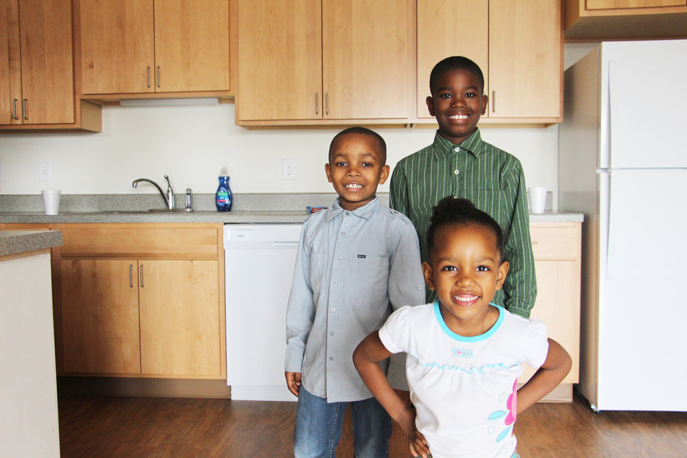 Keyondre (9), Kamryn (8), and Zaniah (5) pose for a photo in their new kitchen inside the Hawthorne EcoVillage Apartment building.  Photo by Megan Nickel.